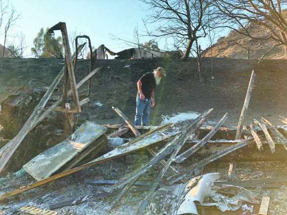 Randy Childs sifts through the ashes of his yurt on the grounds of Camp JCA Shalom in Malibu, one of three Jewish camps there destroyed by the Woolsey blaze.