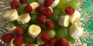 fruit salad in a glass bowl with bananas, raspberries and green grapes