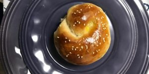 One challah roll on a circular plate
