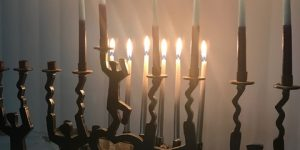 two lit menorahs that look like dancing people holding up the candles