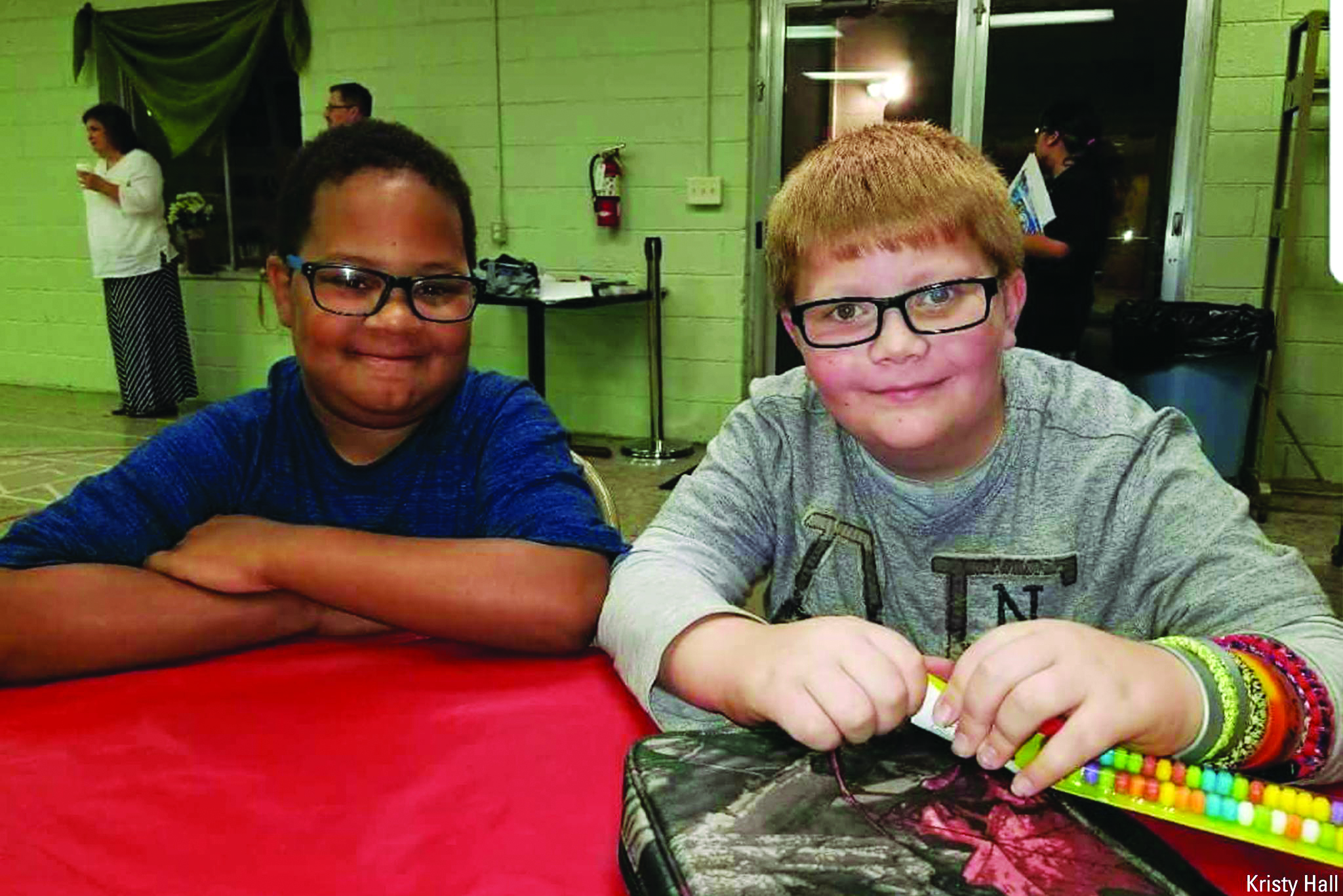 KJ Gross and Kaleb Klakulak sit at a table and smile. One black boy and one white boy with red hair, both with glasses