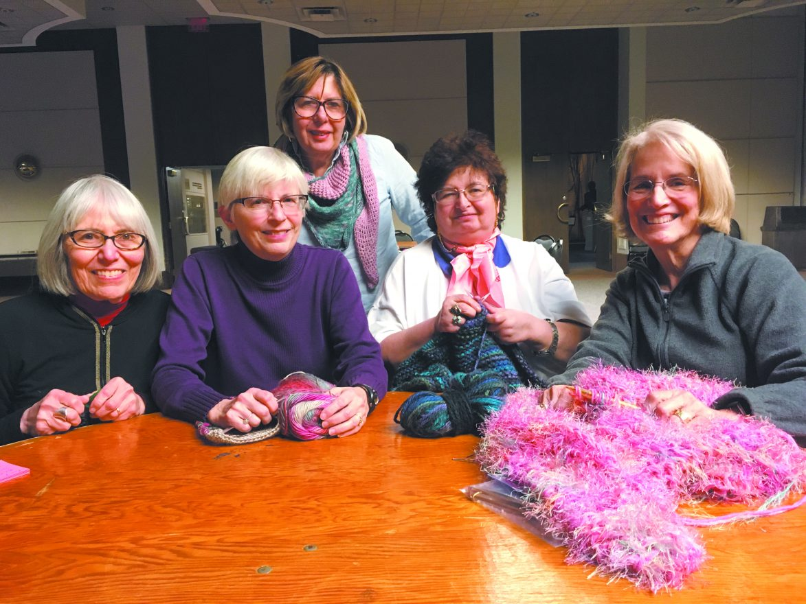 Knitters Lori Bolkosky, Oak Park; Vicki Salinger, Southfield; Liz Kannon, Ferndale; Gila Gelfond, Southfield; and Judy Domstein, West Bloomfield sit together at a table with knitting needles and yarn and smile at the camera