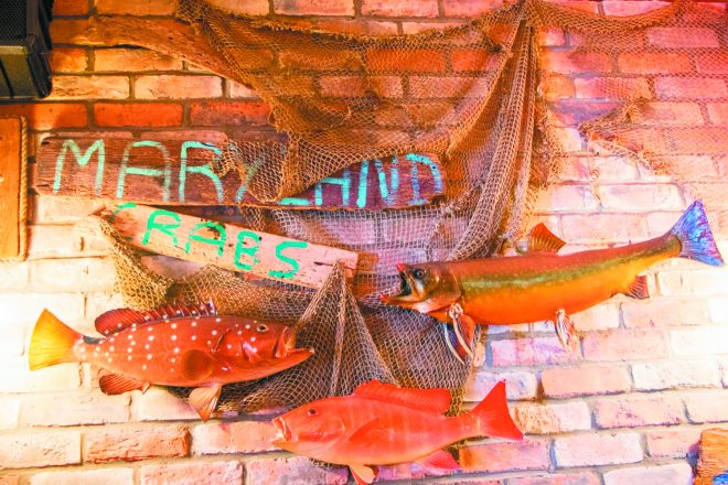 "fish on the wall at O'Brien's Crabhouse and a sign that says ""maryland crabs"" with some fish net around it."