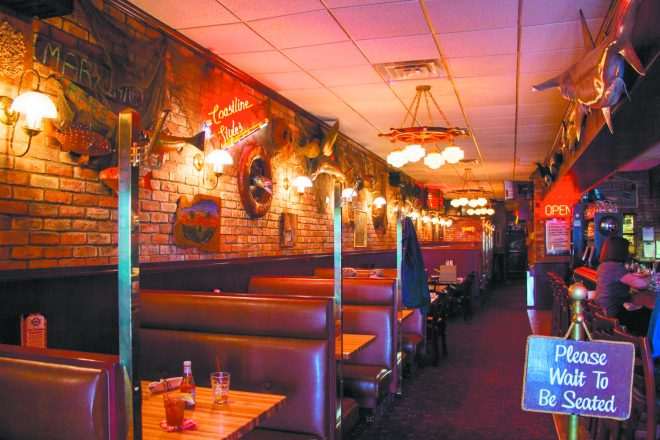 The inside of O'Brien's Crabhouse showing booths in a row with some hanging lights