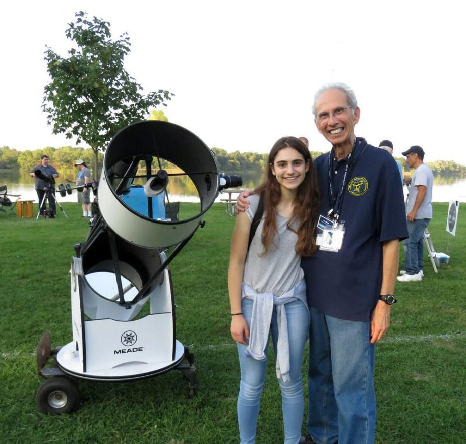 Rebecca Blum and Jon Blum with a large telescope at an open park