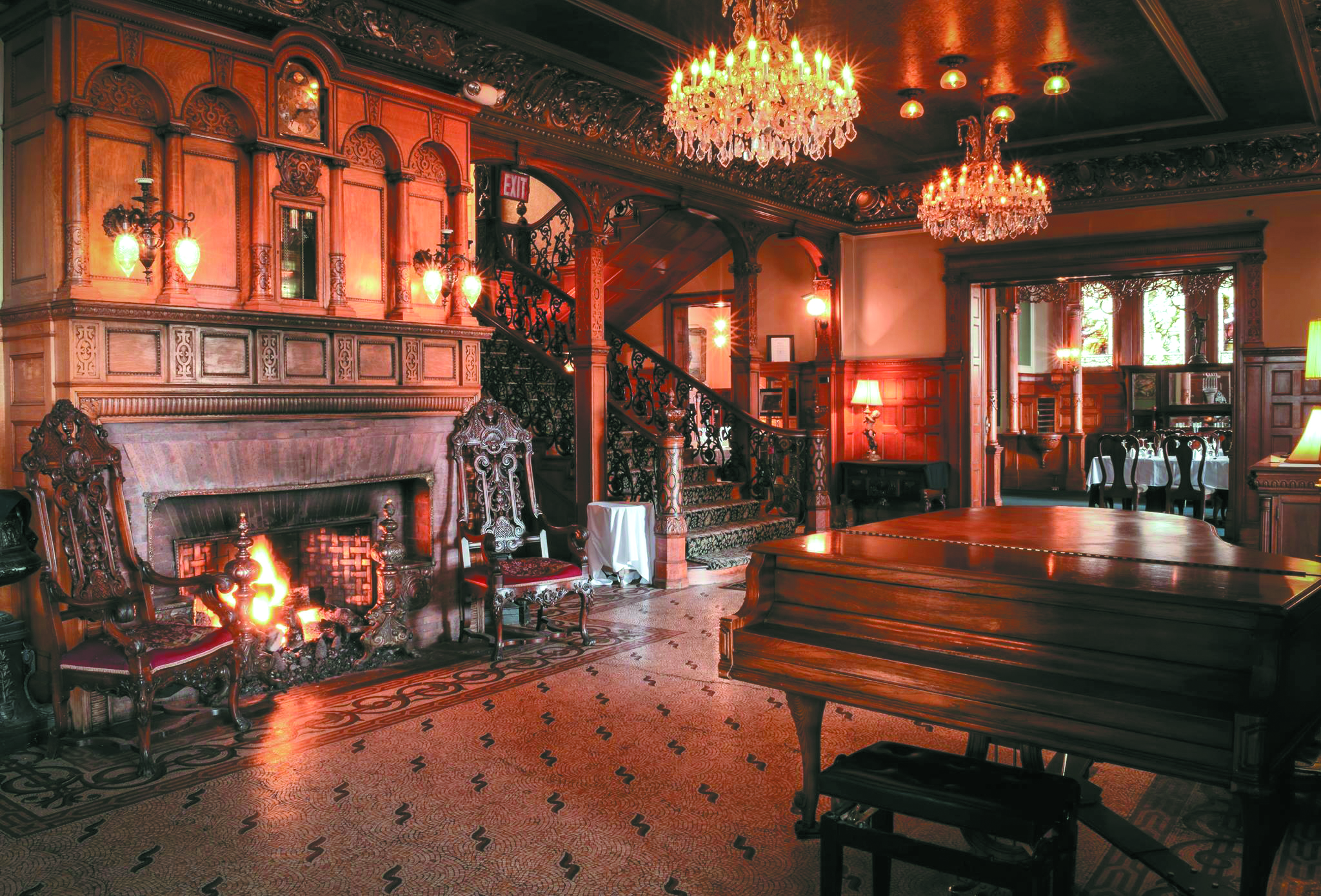 the inside of The Whitney showing a grand piano and fireplace with chandeliers