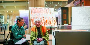 Charlotte Dubin and textile artist Ruth Adler Schnee share a laugh near a pop-up exhibit of Schnee's work.
