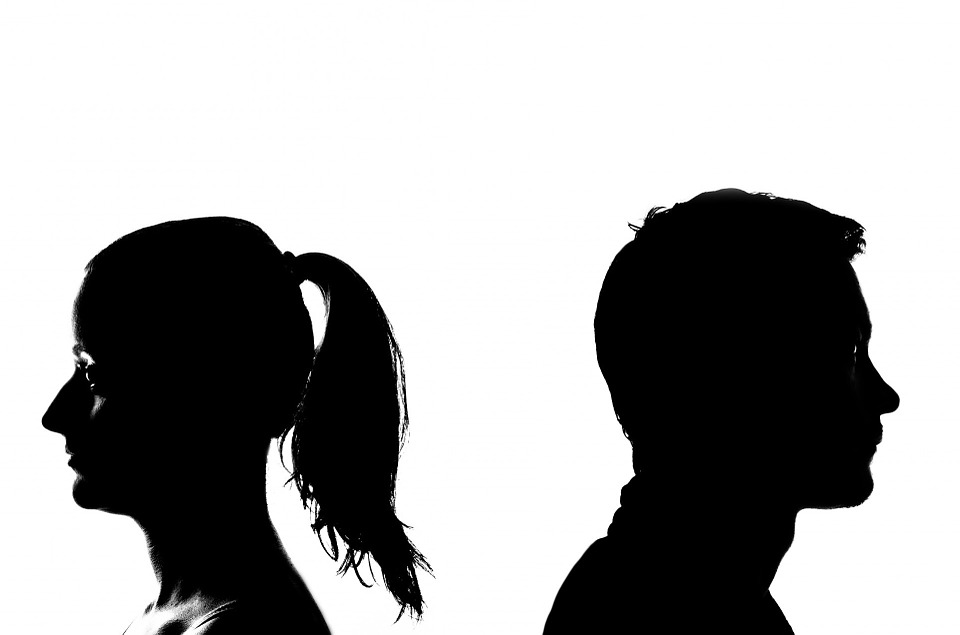 woman turned away from a man seen in silhouette