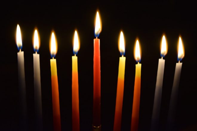 close up on 9 lit candles in a dark room.