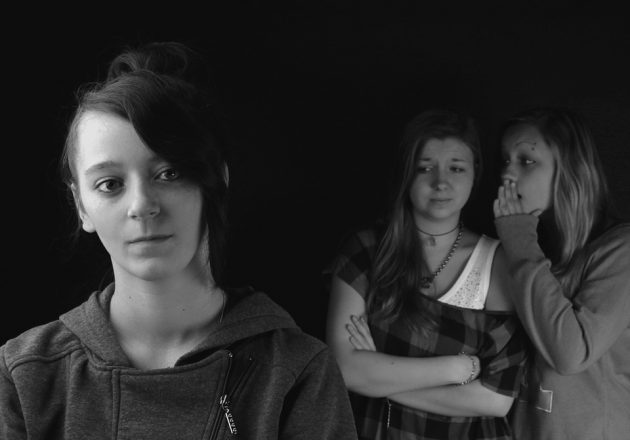 black and white photo of a girl in the front wearing a sweatshirt and looking sad and two girls behind her whispering with arms crossed and staring at the forward girl with discontent.