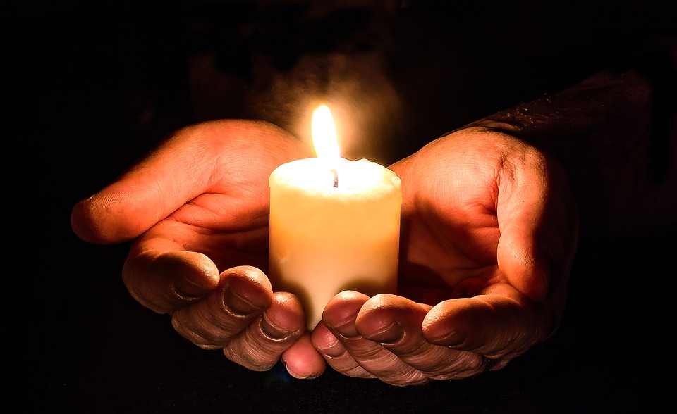 two hands holding a lit candle in open palms.