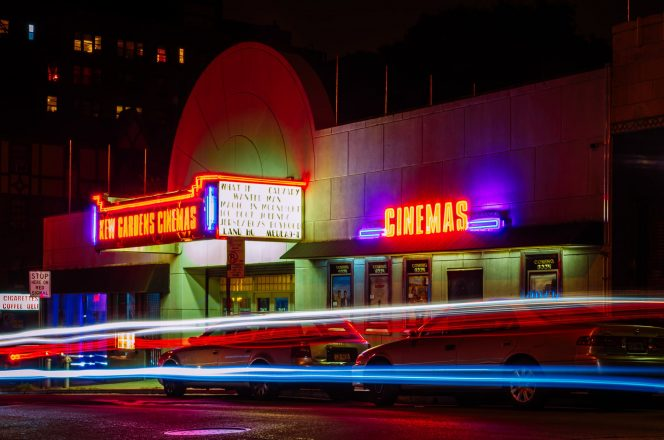 long exposure of the outside of a movie theater showing cinemas at night with cars driving past.