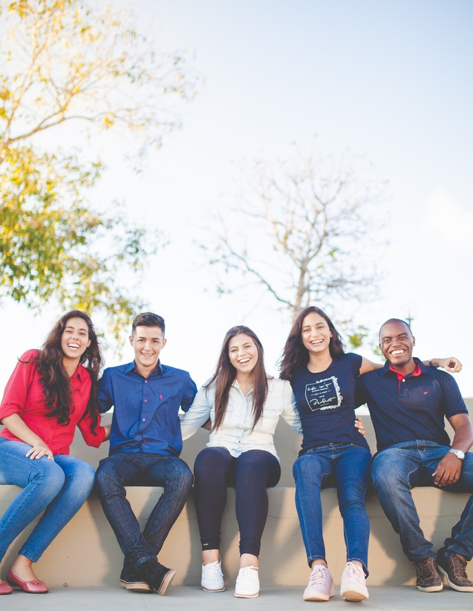 Five students sit on an outside ledge on a sunny, clear day with some trees behind them.