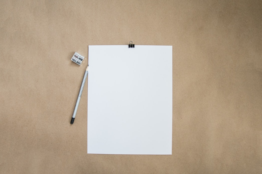 blank paper and pencil with pencil sharpener on a table