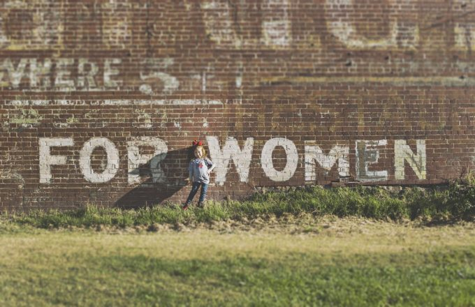 """Little girl standing in front of a brick wall with the words """"for women"""" in front of it"""