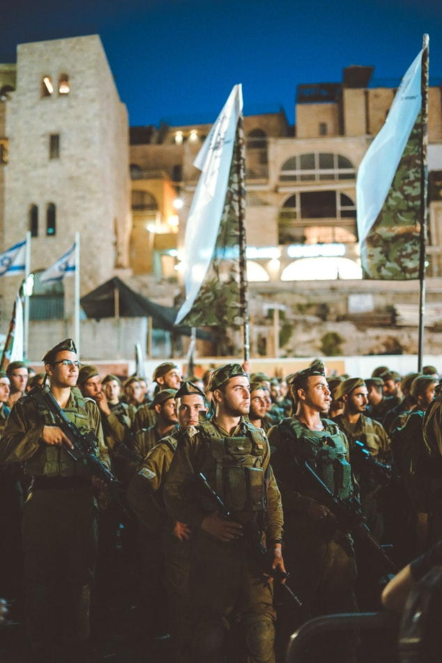 Israeli IDF soldiers stand together with Israeli flags waving behind them