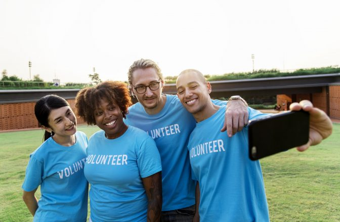 """two men and two women wearing blue shirts that say """"volunteer"""" taking a group photo on a smart phone."""