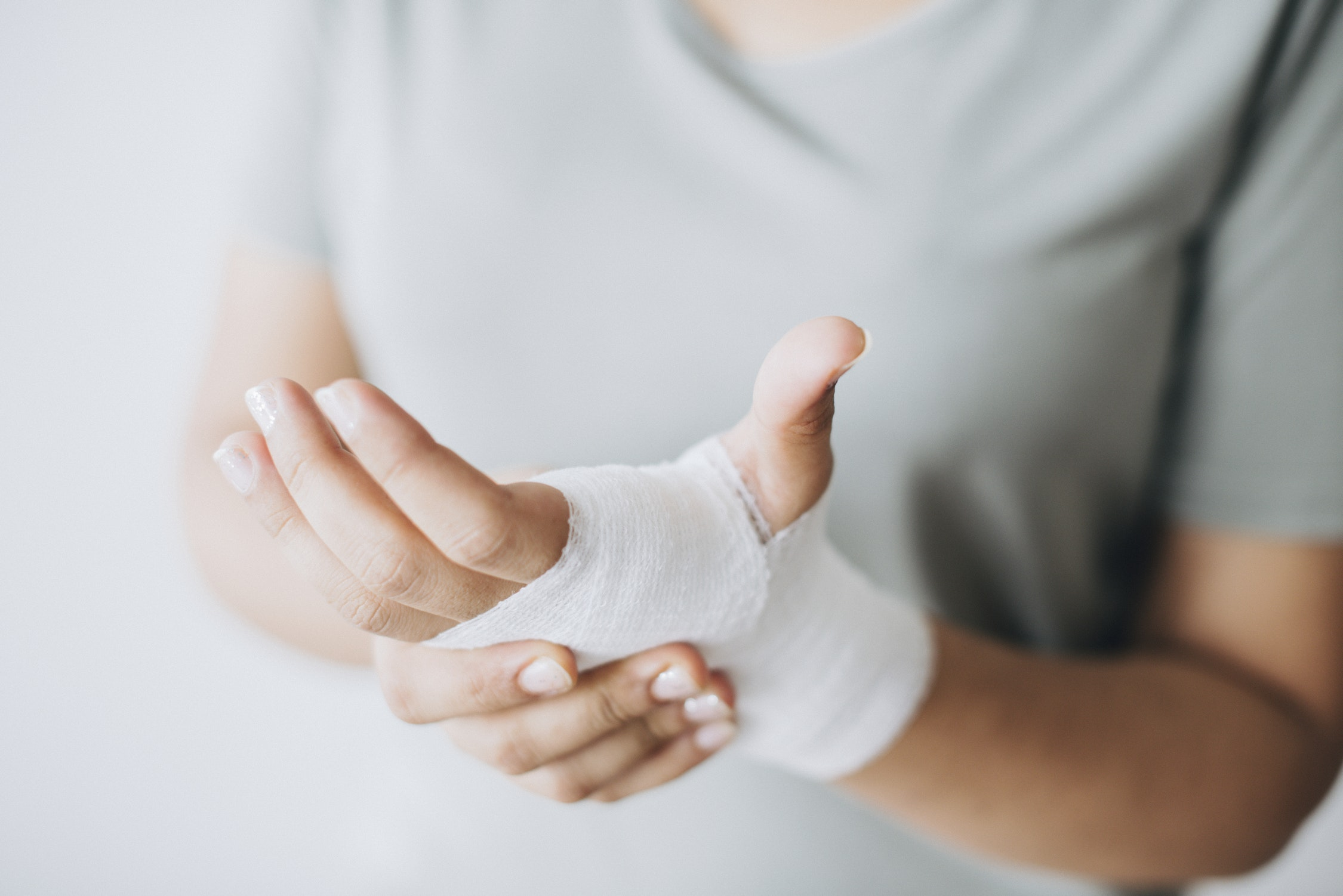 hand holding other hand wrapped in a bandage around the hand and wrist.