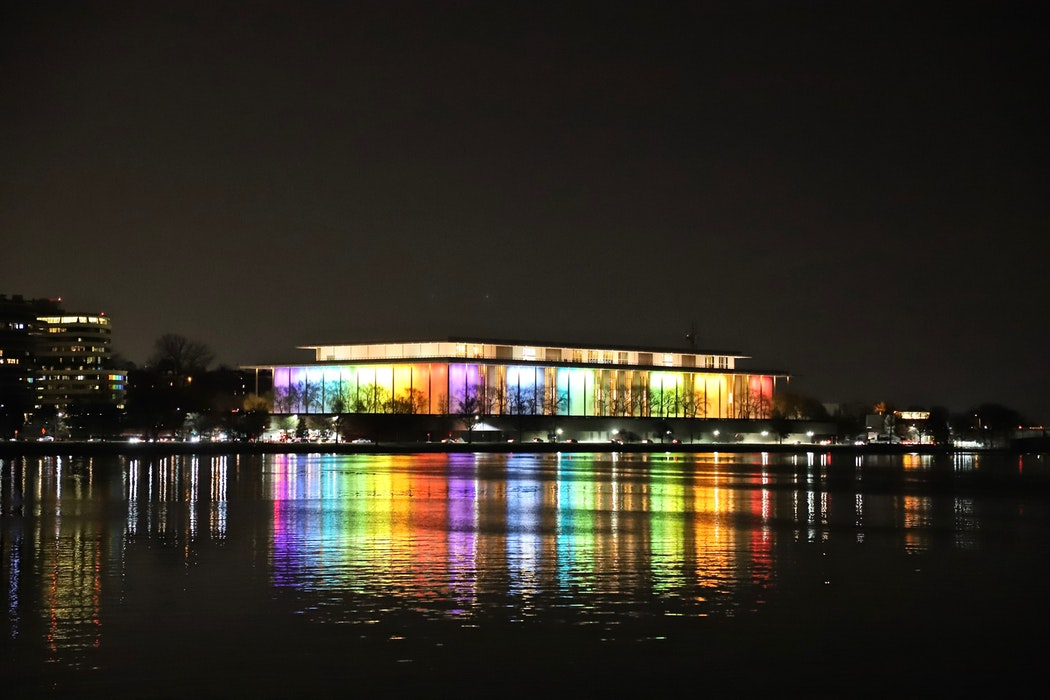 The John F. Kennedy Center, Washington, United States at night seen from across the water with lights in rainbow lighting the building