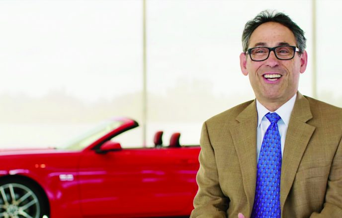 Neil Schloss in front of a Ford convertible