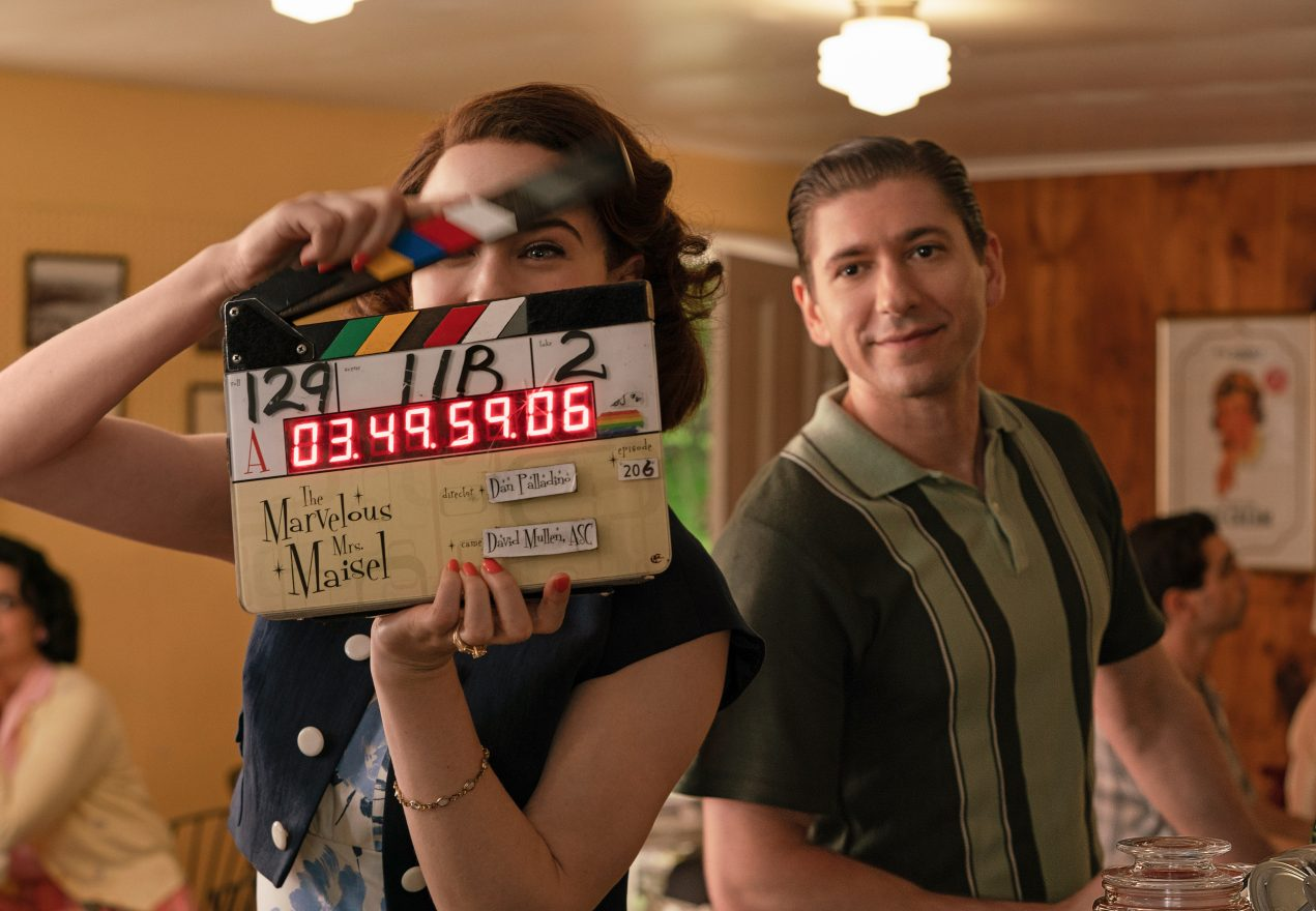 Michael Zegen in a scene from Mrs. Maisel with Mrs. Maisel holding a film clapper.