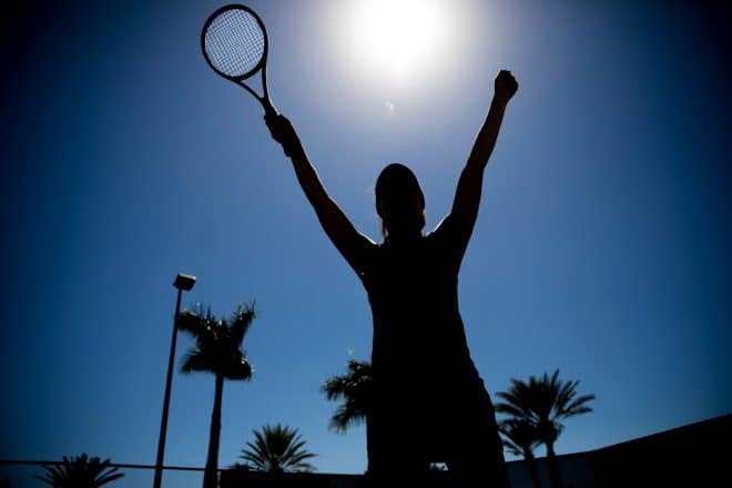 Silhouette of female tennis player standing with arms raised, celebrating victory against the sky