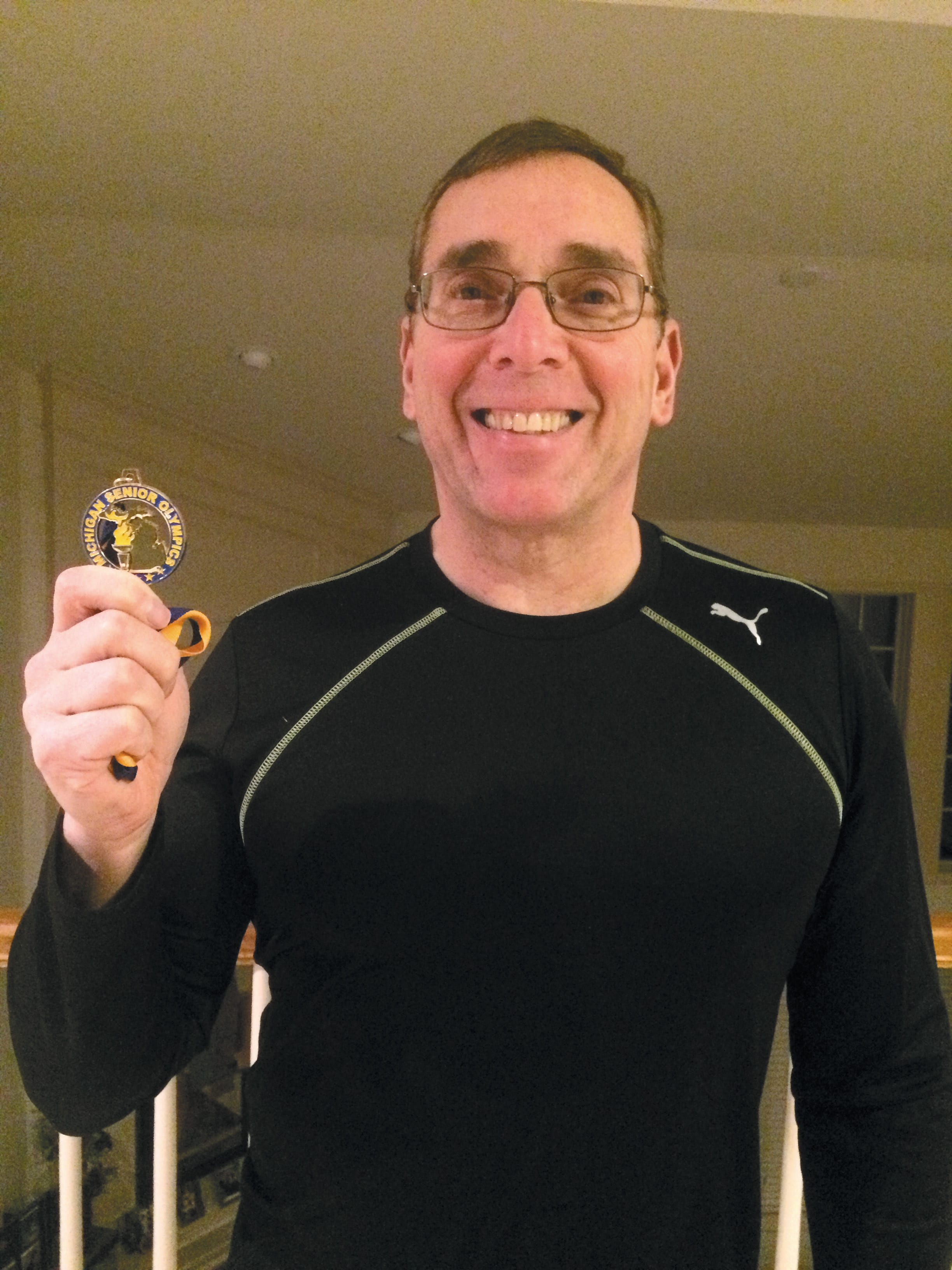 Jeff Ellis shows off his latest Michigan Senior Olympics gold medal.