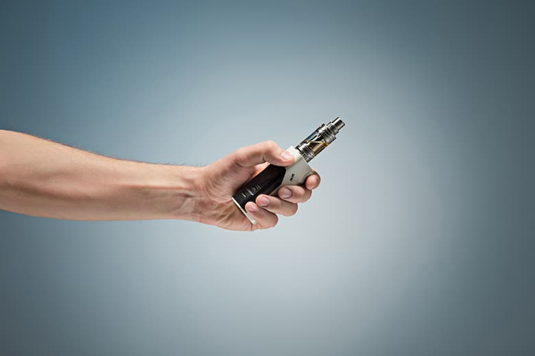 Hand holding an electronic cigarette over a studio background.