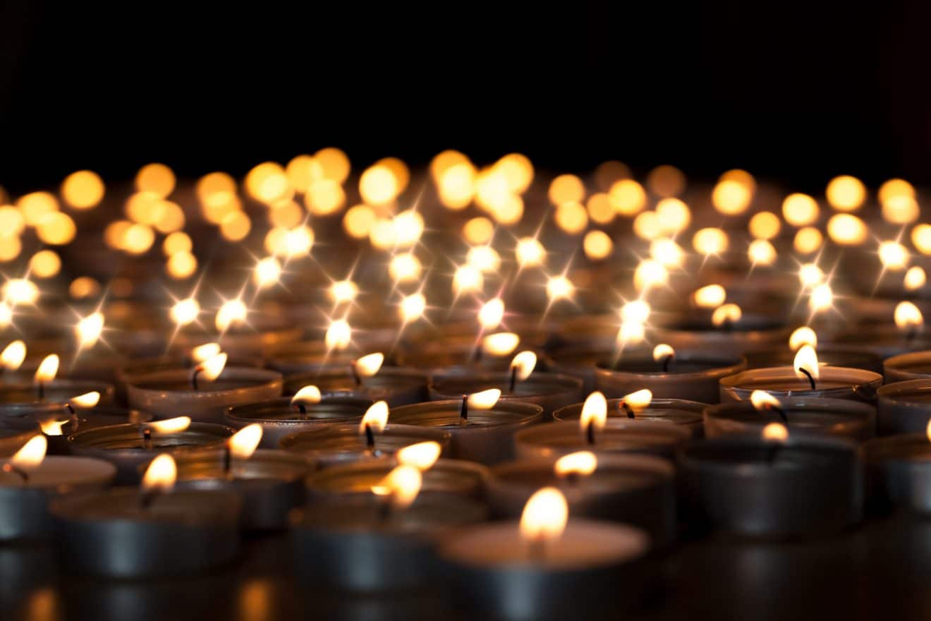 Tealight candles. Beautiful Christmas celebration, religious, or remembrance candlelight image. Romantic candlelit vigil. Selective focus against black background.