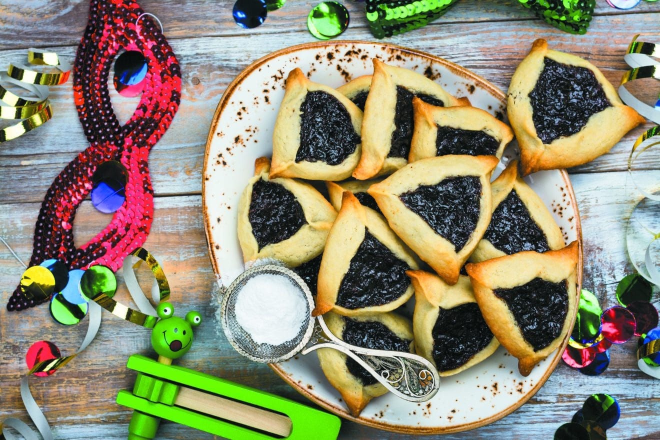 Traditional Jewish Hamantaschen cookies with berry jam. Purim celebration concept. Jewish carnival holiday background