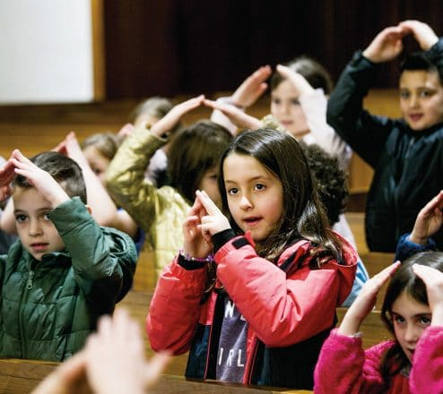 Younger students respond to Hebrew words through music and movement in Temple Beth El's chapel.