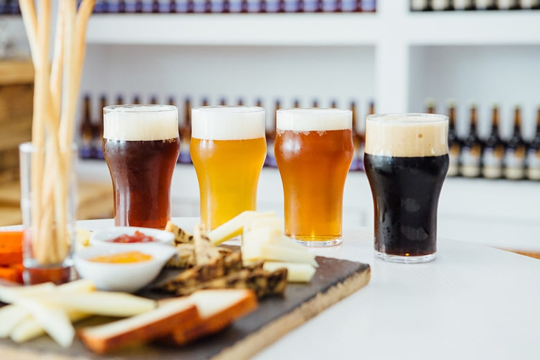 Close-up of four glasses of different craft beer with snack board