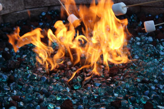 Marshmallows being roasted over a firepit, bright fire with blue stones for Lag B'Omer