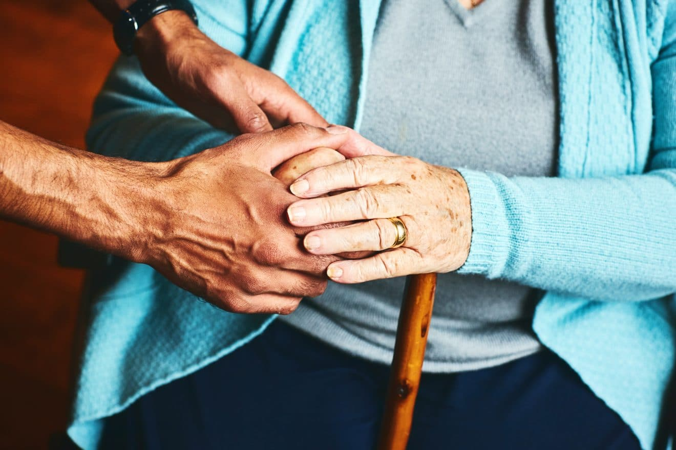 Close up of male carer holding hands of senior woman