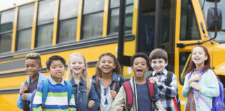 elementary school children smiling in front of a school bus