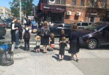Women and children wait at a crosswalk in the Orthodox neighborhood of Borough Park, Brooklyn