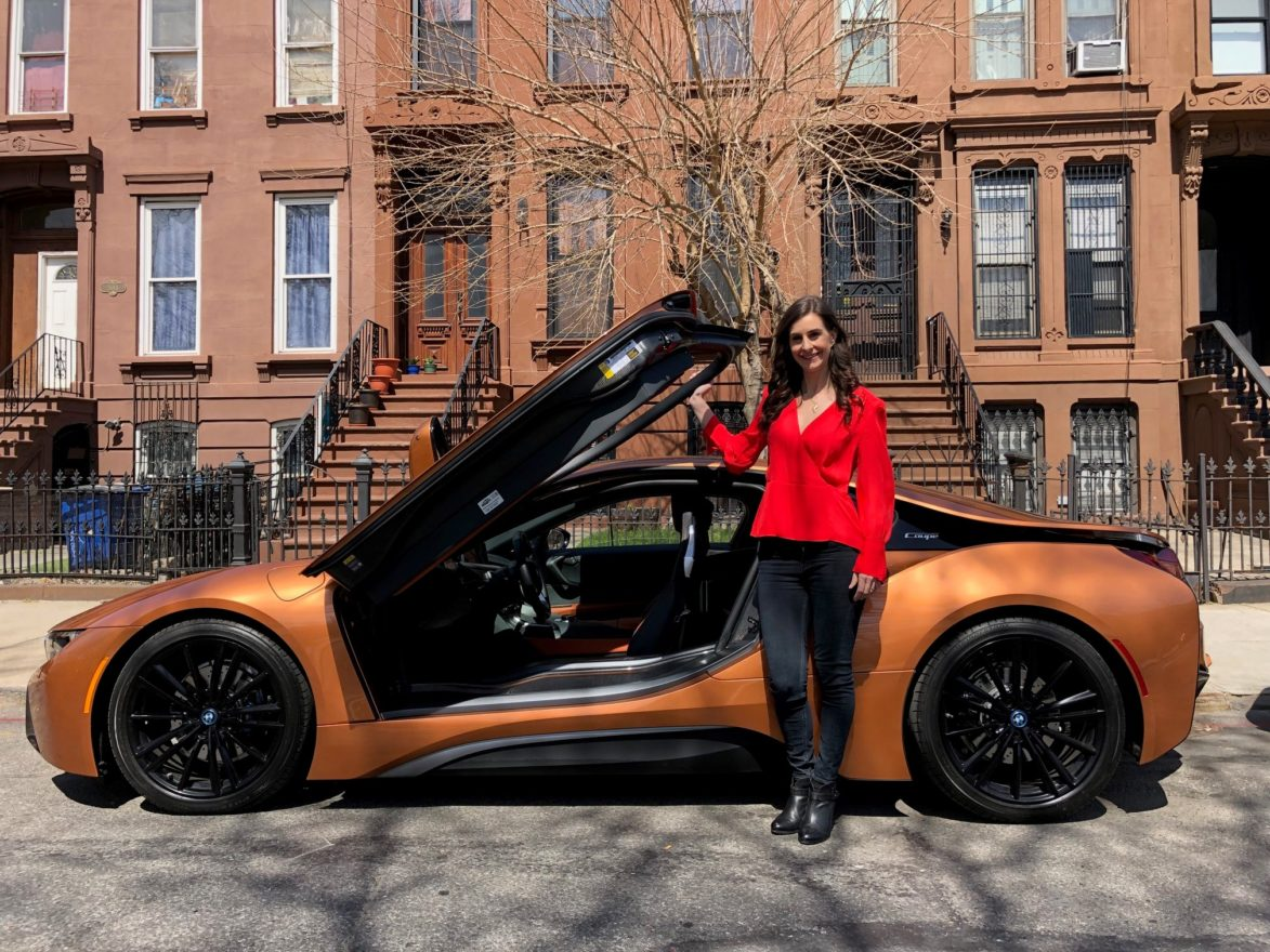 Tamara Warren standing in front of orange car