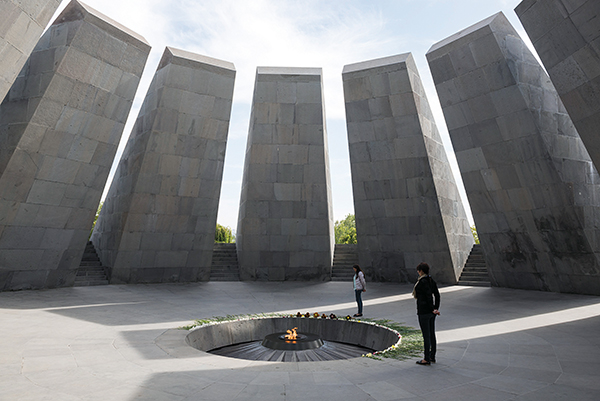 Two visitors stand next to the eternal flame at the Armenian Genocide Memorial in Yerevan, Armenia.