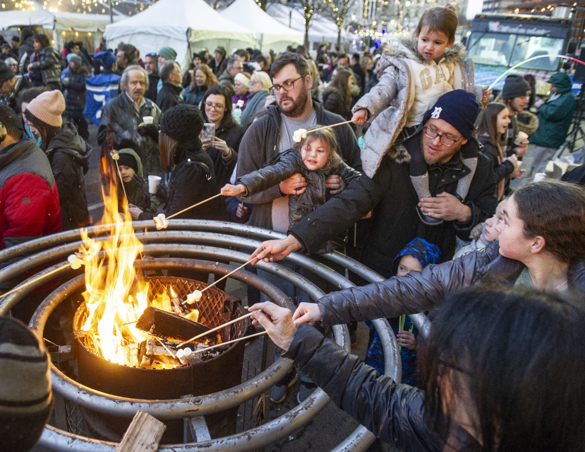 Families roasting marshmallows at Menorah in the D