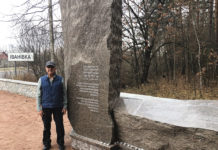 Alex Goldis standing beside memorial in Ukraine
