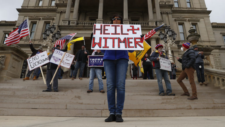 Dawn Perreca protests on the front steps of the Michigan State Capitol building in Lansing, Mich., Wednesday, April 15, 2020.