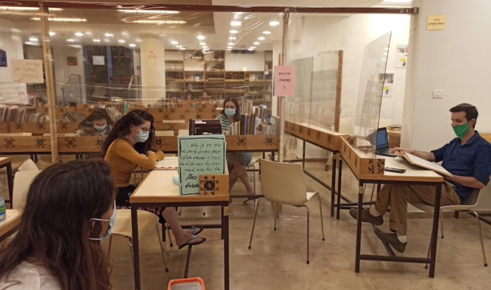 Students at Nishmat in Jerusalem wear masks and are separated by Plexiglas barriers to protect against the coronavirus. (