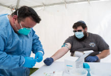 Volunteer gets ready to draw blood from a donor.