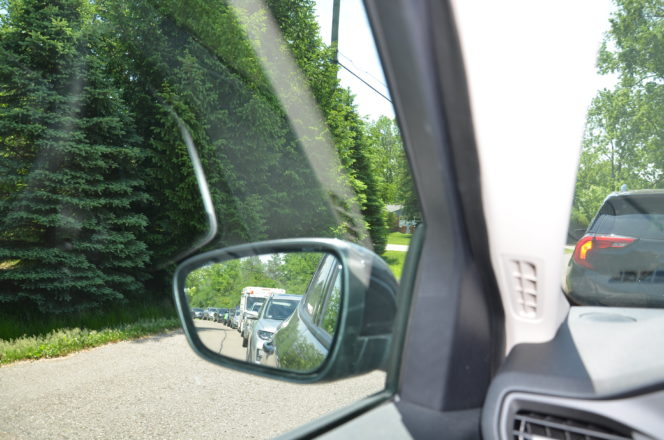 The parade of cars, seen from a side view mirror
