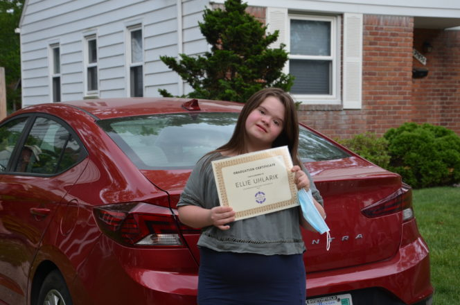 Ellie Uhlarik holds up a graduation certificate from Friendship Circle.