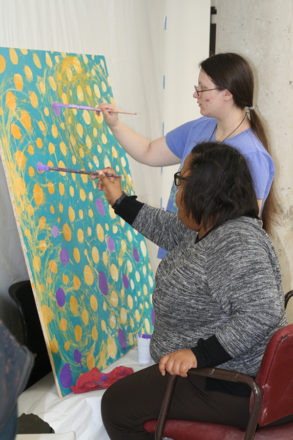 Kadima artists Madison Dunbar (sitting) and Brittany Strickland work collaboratively on a mural painting.