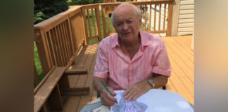 Survivor Sandor Adler enjoys the adult coloring book that came in his gift bag.