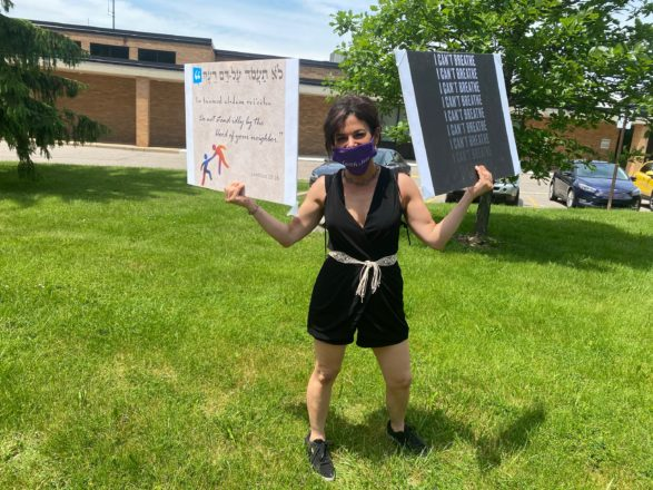 Rabbi Rachel Lawson Shere of Adat Shalom Synagogue held two signs