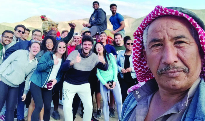 MSU students pose for a selfie with a Bedouin guide on a study abroad trip to Israel.