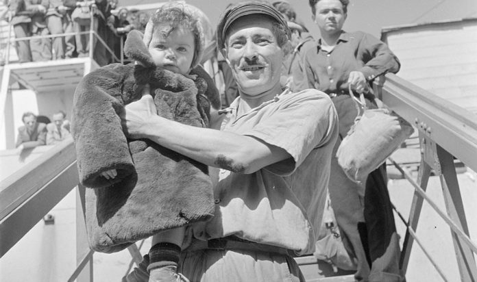Israeli worker carries young child from Bulgarian ship.